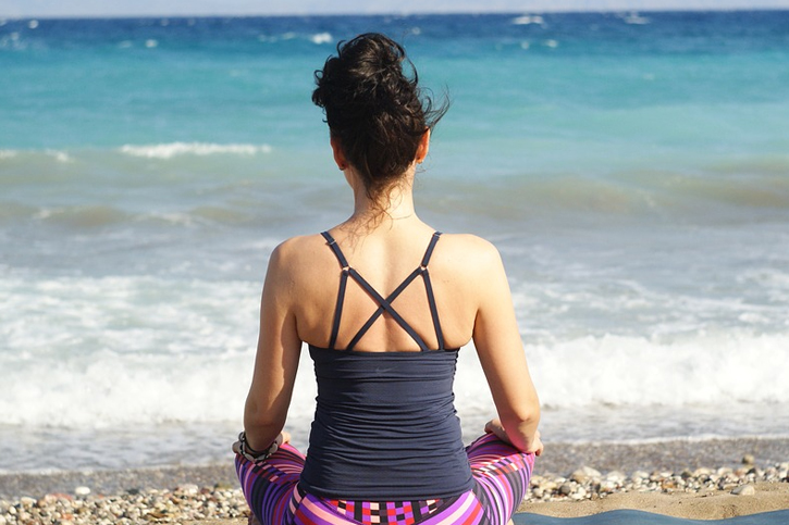 woman meditating beach